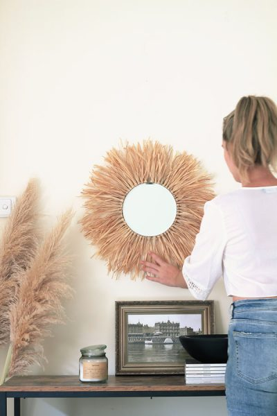 Get the boho vibes in your home! How to make this tropical-inspired, round raffia sunburst mirror.